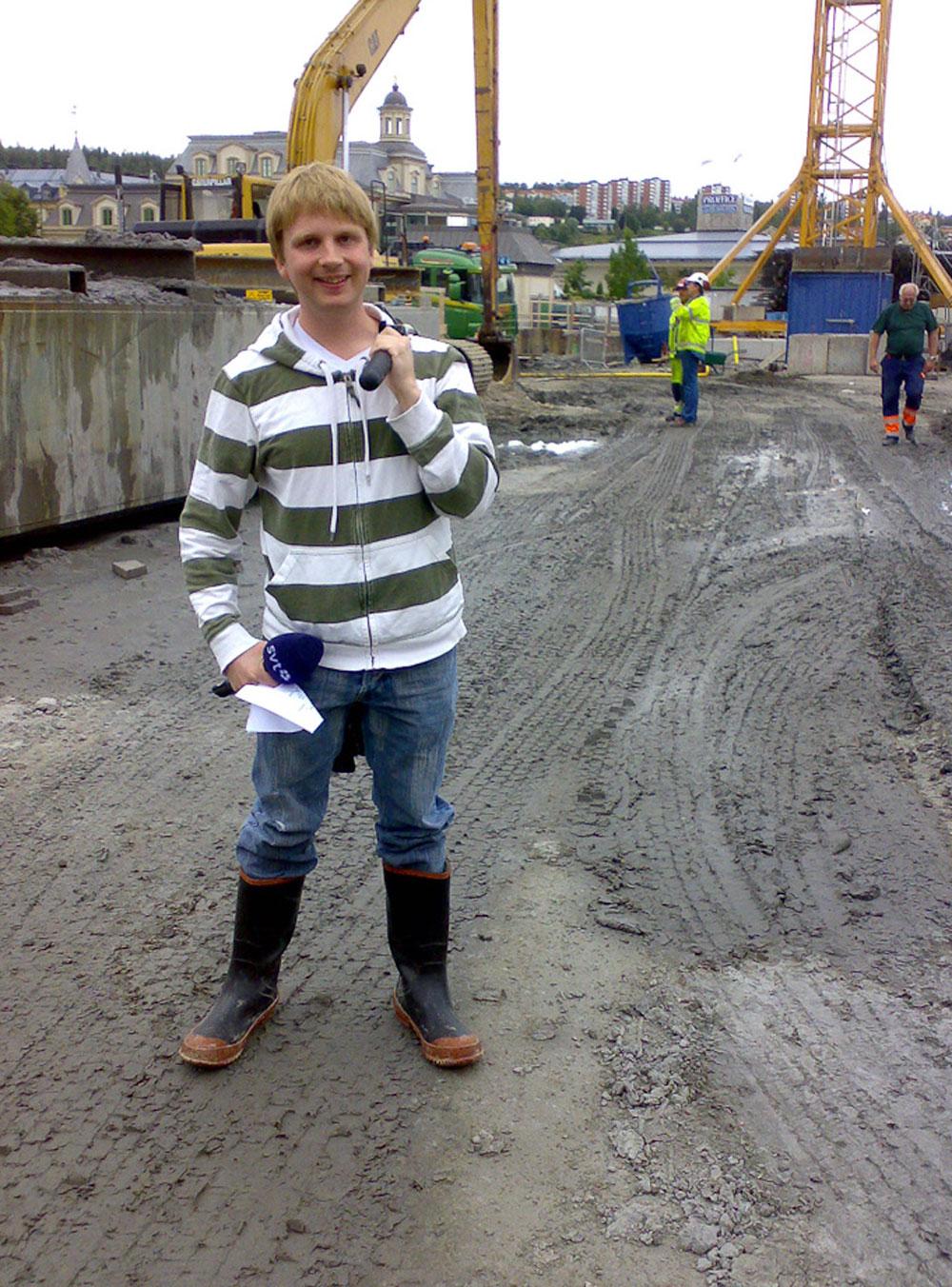 Backa Elias Bondpä på byggarbetsplats med SVT-mikrofon, stativ och gummistövlar.